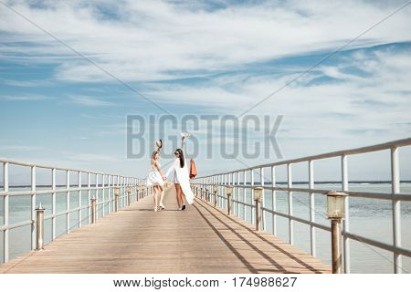Two happy young women holding hands, walking on pier and looking back
