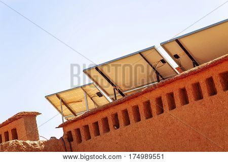 Closeup view on solar panel with desert house