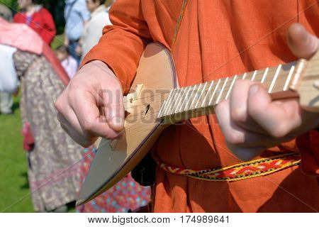 Balalaika in hands of the man dressed in a national Russian suit close up
