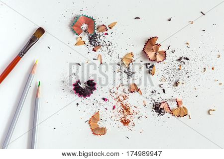 Creativity Concept Image of Brush color Pencils and shaped wood Chips and Shavings of sharpening a pencil on white Table