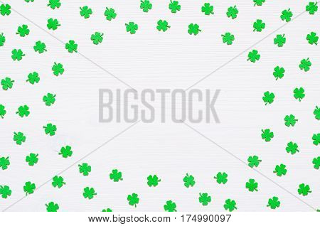St Patrick's Day concept. St Patrick's Day background - green quatrefoils on the white wooden surface with free space for text. St Patrick's Day background with St Patrick's Day symbols. St Patrick's Day festive background