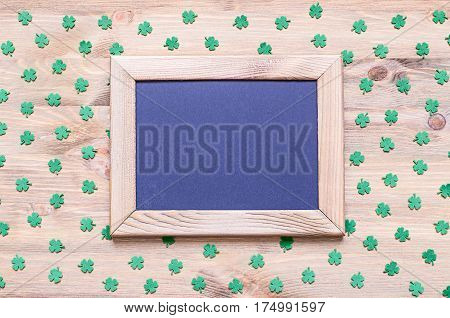 St Patrick's Day. St Patrick's Day background - wooden frame with free space for text and green quatrefoils on the wooden surface. St Patrick's Day background with St Patrick's Day symbols. St Patrick's Day festive background