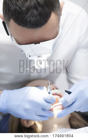 Dental cure. Molar treatment. Young female patient visiting dentist office.