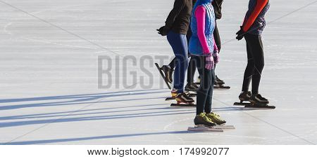 Speed skating sportsmen on competition- ice rink at winter sunny day - children's sport concept, telephoto