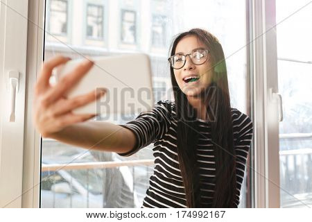 Happy Asian womann eyeglasses which making selfie on phone and sitting on windowsill in cafeteria