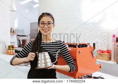 Smiling Asian barmaid in eyeglasses which standing with kettle and looking at camera