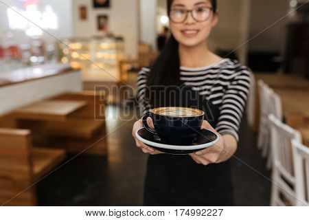 Asian barmaid which extends the cup of coffee at camera. Focus on cup