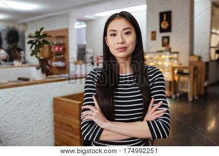 Asian woman in sweater which standing with crossed arms in cafeteria and looking at camera