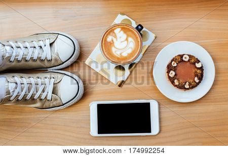 Top view of wooden board with phone, coffee, cake, gumshoes and notebook