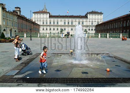 Childern Plying With A Ball On A Fountain