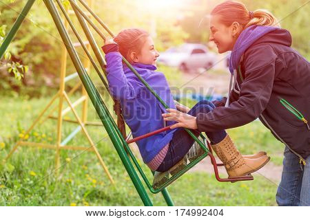 Young Mother Little Daughter on Seesaw in Spring Park Sprtive Casual Clothing Woman and Little Child Outdoor Sunny Day green Grass and shining Sun on Background.