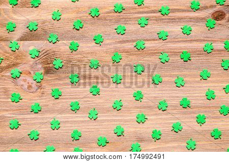 St Patrick's Day background - green quatrefoils on the natural wooden texture background. St Patrick's Day background with St Patrick's Day symbols. St Patrick's Day concept - St Patrick's Day background