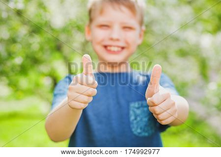 Handsome cheerful 9 years old boy giving two hands with thumbs up into camera as symbol of success. Closeup of fingers with focus at them and blurry face of blonde cute happy kid with great smile.
