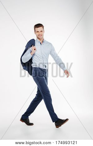 Vertical image of Smiling man in business clothes which walking in studio and looking at camera. Isolated white background