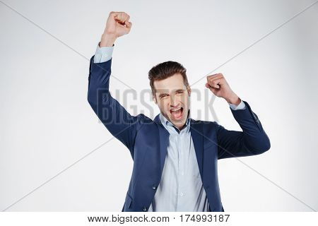 Happy man in blue suit which screaming in studio and looking at camera. Isolated white background