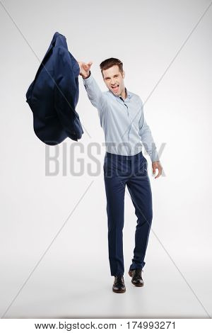 Vertical image of man in business clothes which throws the jacket at camera. Isolated white background