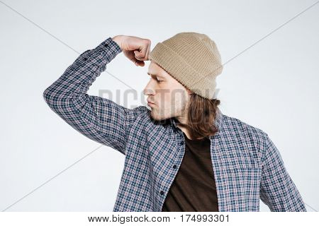 Serious hipster which showing his bicep and looking at him. Isolated gray background