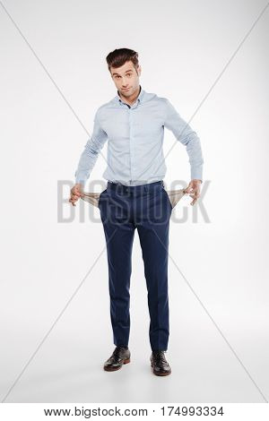 Vertical image of Man in business clothes which posing in studio and showing empty pockets