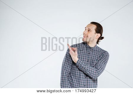 Happy man in shirt which pointing and looking away. Isolated gray background