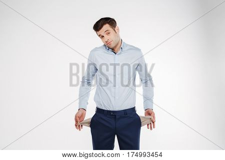 Upset man in business clothes which showing empty pockets and looking at camera. Isolated white background