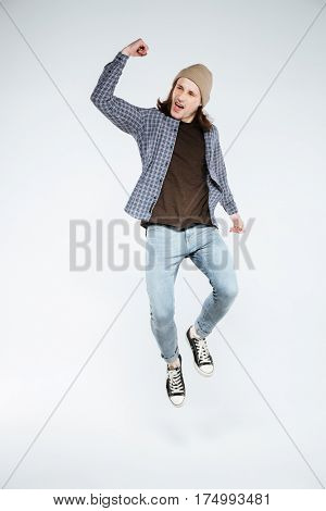 Vertical image of so happy hipster which jumping in studio. Isolated gray background