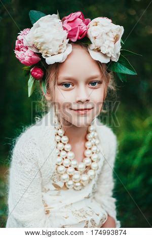Summer portrait of a little girl with wreath of peony flowers. Fashion photo. Natural beauty. Russian girl. Authentic portrait.
