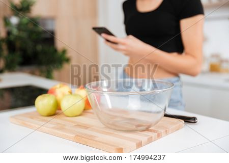 Cropped image of woman which standing in kitchen and using phone. Focus on the table