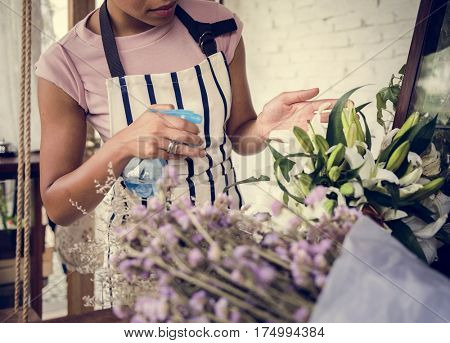 Woman Spraying Flowers to Refreshing in Flora Shop