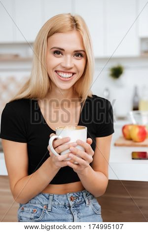 Vertical image of Woman which sitting in kitchen and holding cup coffee while looking at camera