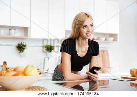 Smiling woman which standing in kitchen with smartphone and looking away