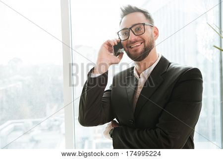 Bearded business man in suit and eyeglasses which talking on the phone near the window