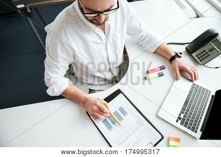 Top view of man in white shirt and eyeglasses which writing something while sitting by the table with laptop computer in office
