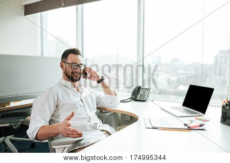 Smiling Man in shirt and eyeglasses which sitting by the table and talking on phone in office