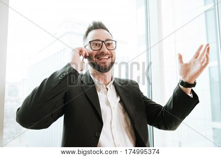 Happy Bearded business man in suit and eyeglasses which talking on phone with window on background