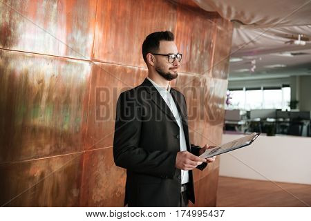 Side view of business man in suit which standing near the wall in office with clipboard in hands