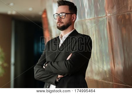 Man in suit and eyeglasses which standing in office with crossed arms