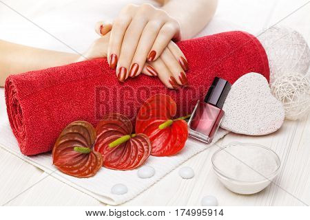 Luxury red manicure with oil and decor, red calla flower and towel on the white wooden table.