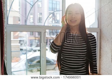 Asian woman in sweater which posing near the window in cafeteria and looking at camera