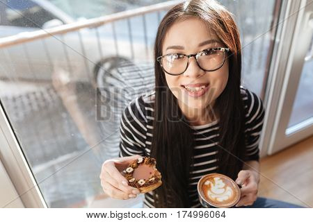 Top view of Asian woman in eyeglasses which sitting with cake and cup of coffee on windowsill in cafeteria