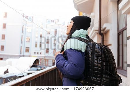 Side view of Young Asian woman in warm clothes and with backpack which standing on the street and looking away