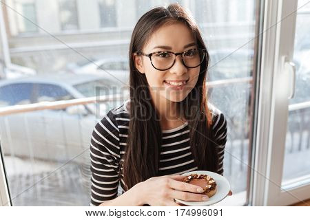 Smiling Asian woman in eyeglasses which sitting on windowsill in cafeteria with cake in hand and looking at camera