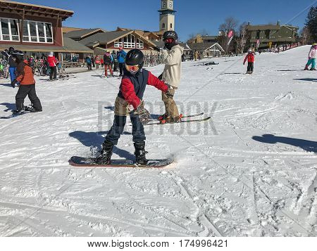 Stratton VT March 05 2017: Kids one on a snowboard the other on skiis are at the end of the skiing run approaching a chair lift.