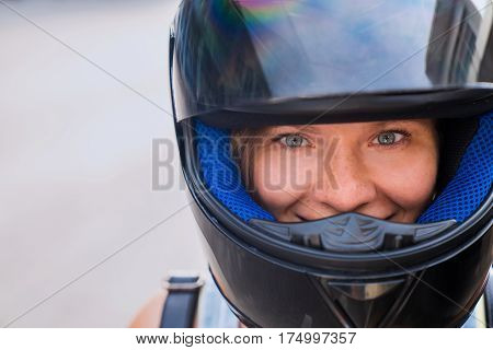 The concept of protection and safety on the road. A girl with beautiful eyes and a happy face in a black helmet with an open visor.