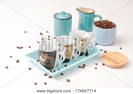 Dishes for coffee. Three cups for different kinds of coffee on a tray. A cup with coffee beans. The grains of coffee are scattered on the table. The lid with the inscription Coffee. Two cups with the inscription sugar and milk. All for Coffee