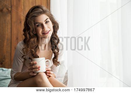 Cheerful young lady holding white mug and looking at camera. Horizontal indoors shot.