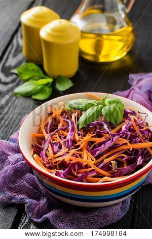 Fresh vitamin salad of red cabbage (scotch kale) with carrot and basil on a dark wooden background. It is used in dietary and vegetarian food. Vertical selective focus