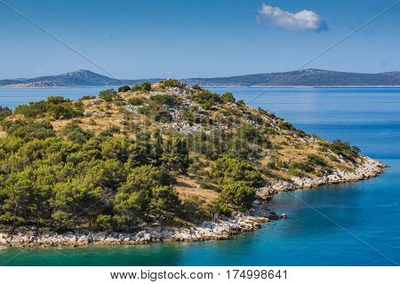 Small island in adriatic sea in summer. Clear cristal water