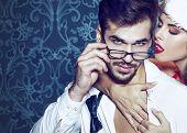 Sexy santa woman seduce young man in tux at Christmas poster