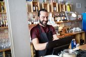 small business, people and service concept - happy man or waiter in apron at counter with cashbox working at bar or coffee shop poster