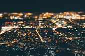 True tilt shift shooting of night metropolis from very high above: multiple warm colorful lights strong bokeh in background street of residential district in focus in foreground poster